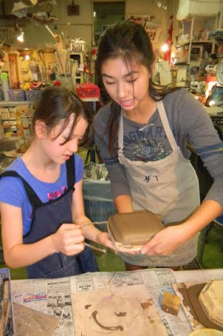 Mai (12) assisting a 5th grader with making her plate.
