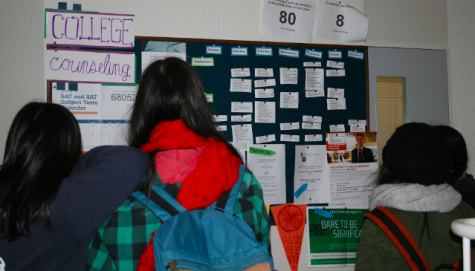Students Staring at the College Counseling Bulletin Board