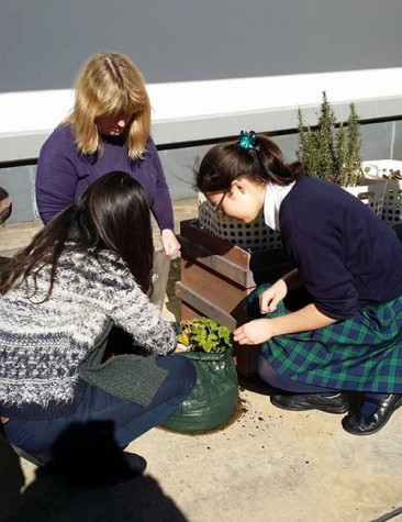 Ms. Pomroy and students planting vegetables