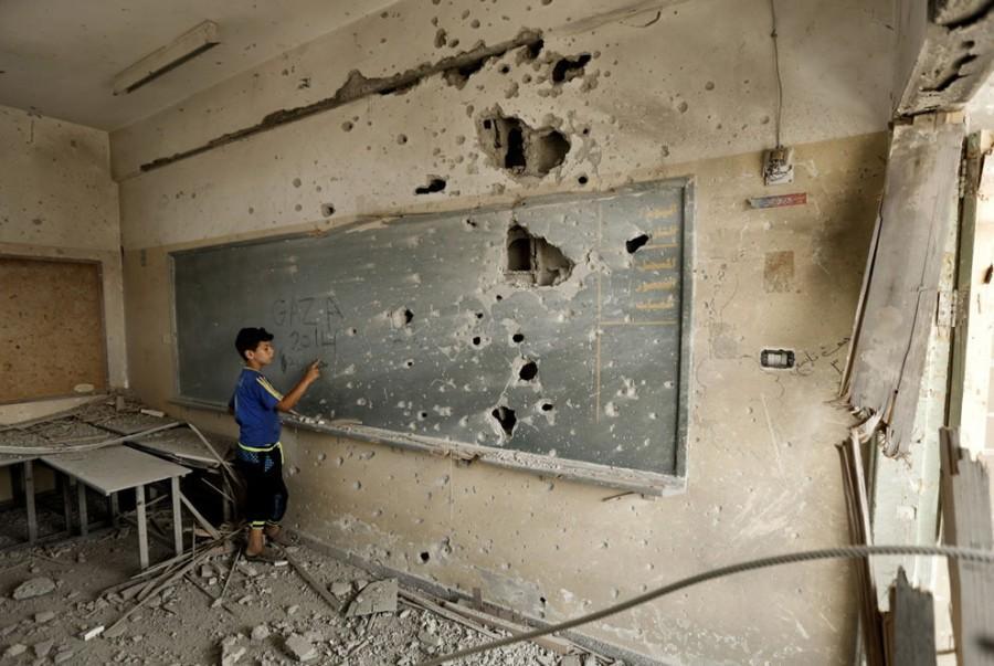 Palestinian boy in heavily damaged Sobhi Abu Karsh school in Gaza City (August 2014)