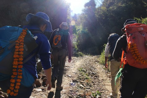 The group hikes up a trail to their campsite with marigold embellished hiking packs and sun hats.
