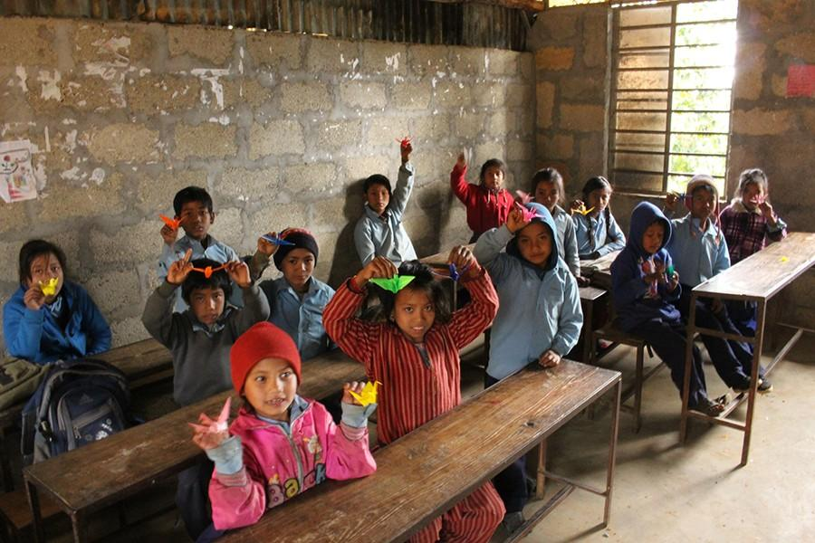 Kids from Shree Manakamana Primary School hold up paper cranes that ISSH students taught them to make.