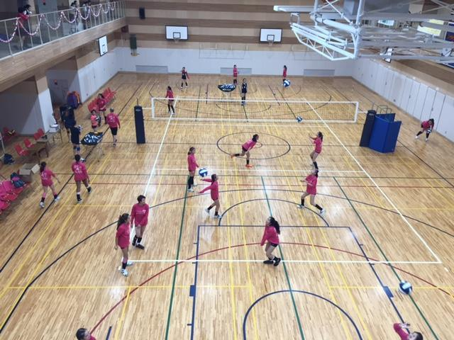 The Junior Varsity teams warm up in their pink T shirts.