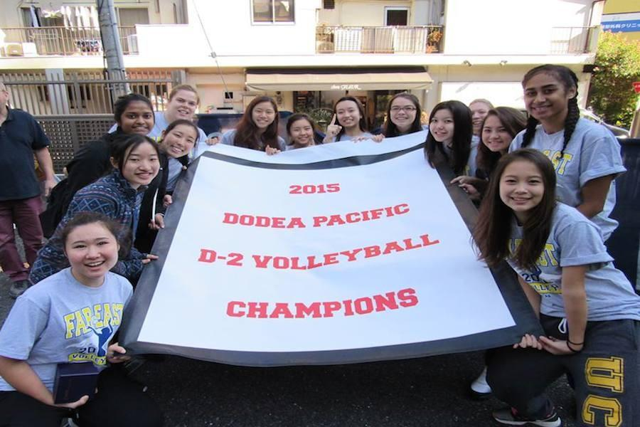Symbas volleyball team presents their championship banner.