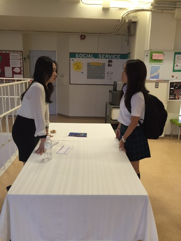 Mirei (11) talks to a college rep from Hong Kong University of Science and Technology.