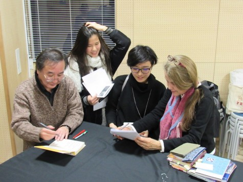 """The Japanese translator for """"Habibi"""" (Left) and Ms. Nye (Right) sign books for students"""