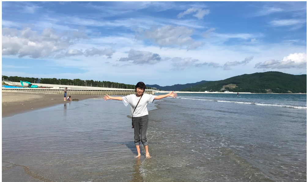 The writer's grandmother posing on the beach in Ishinomaki. On the far left there is a green excavator and the white horizontal line along the center of the picture is the dike.