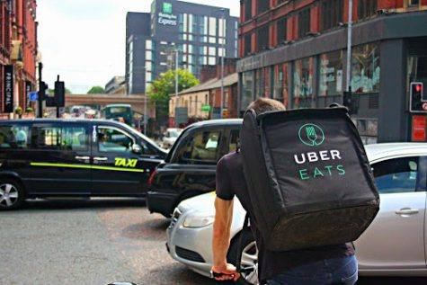 """UBER Eats Delivery Cyclist Riding Through a Busy Oxford Road in Manchester"""